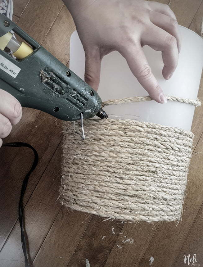 Holding a hot glue gun and gluing sisal rope on the trash can