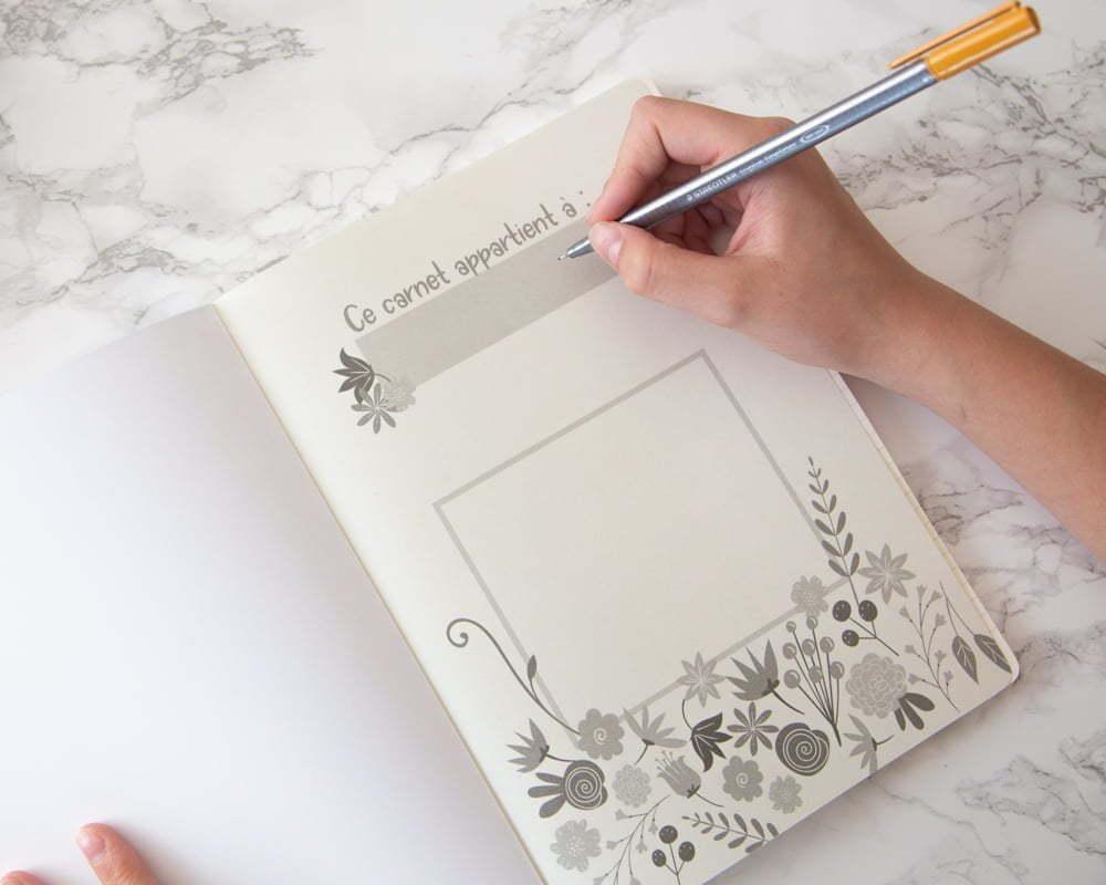 """L'intérieur du carnet de notes. Il est indiqué """"Ce carnet appartient à"""" et il y a un carré pour une note personnelle."""