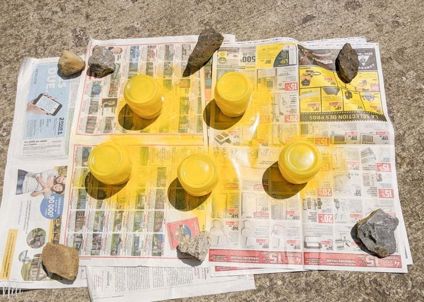 5 mason jars upside down on newspaper painted in yellow for DIY Pikachu Mason Jar gifts