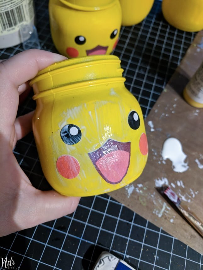 Gluing the eyes, mouth and cheeks with ModPodge to make DIY Pikachu Mason Jar gifts.