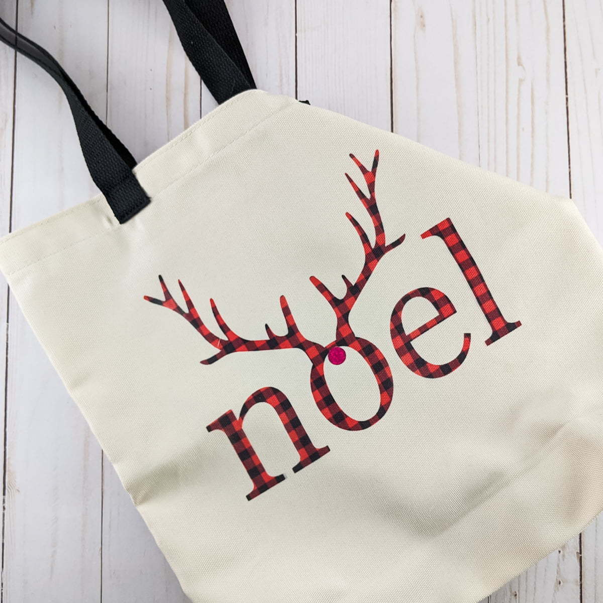 Sac avec l'inscription Noel en carotté rouge et noir avec un panache