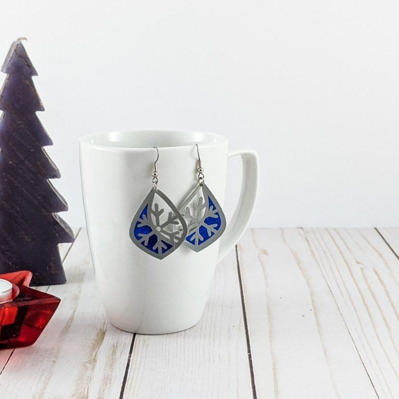 boucle d'oreilles en simili cuir et vinyle bleu accrochées sur une tasse avec un sapin et une chandelle en étoile