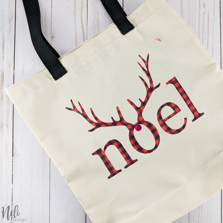 Bag with the writing Noel in red and black buffalo check with antlers.