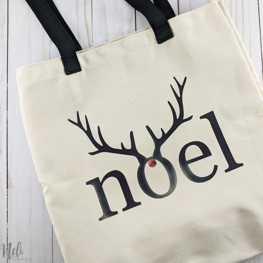 Bag with the writing Noel in black with antlers.