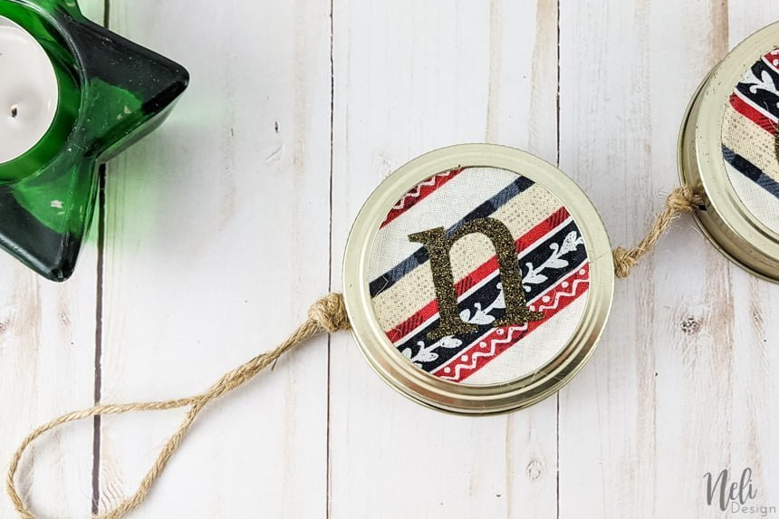"DIY Mason jar lids Christmas craft Each lid has a letter that creates the word ""Noël"""