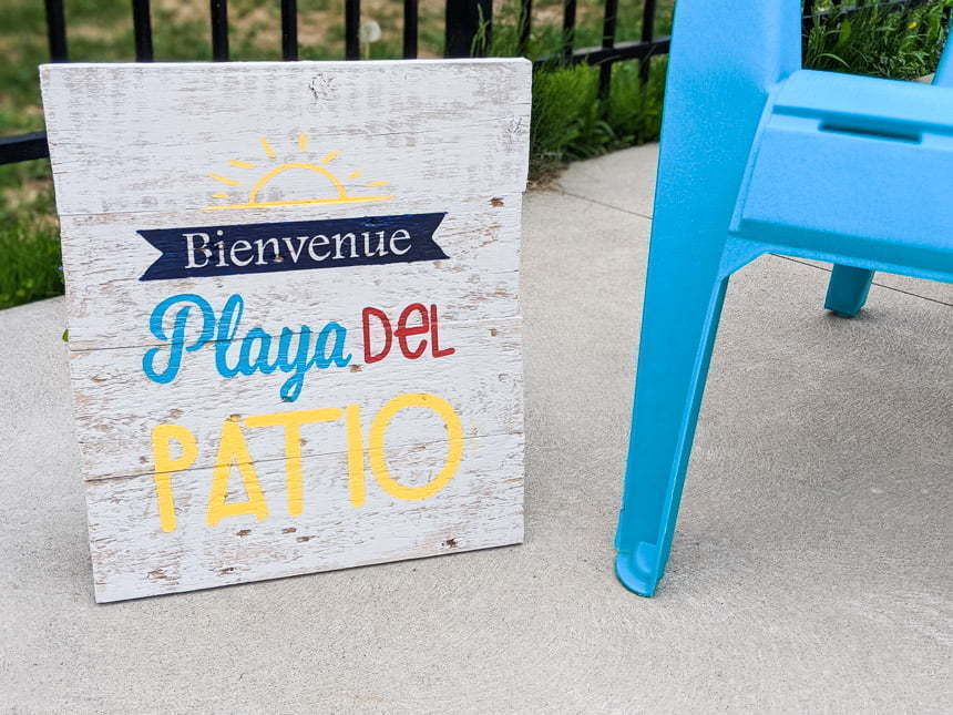 Painted Wood sign made with a Cricut Stencil saying Welcome Playa del patio next to a adirondack chair