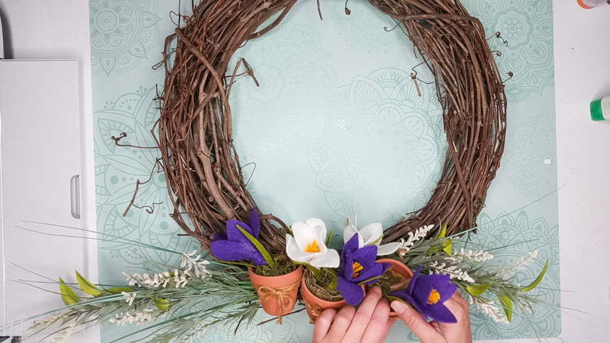 Removing the spring crocus flowers from the wreath to add the DIY chrysanthemum paper flowers to the grapevine wreath