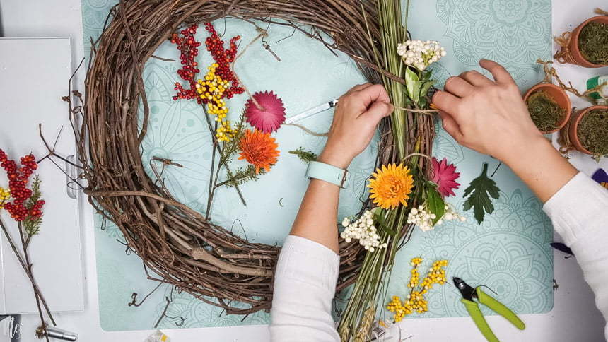 Using knots to attach the DIY chrysanthemum paper flowers to the grapevine wreath