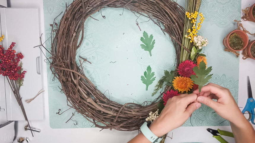 Using wires to add the DIY chrysanthemum paper flowers leaves to the grapevine wreath