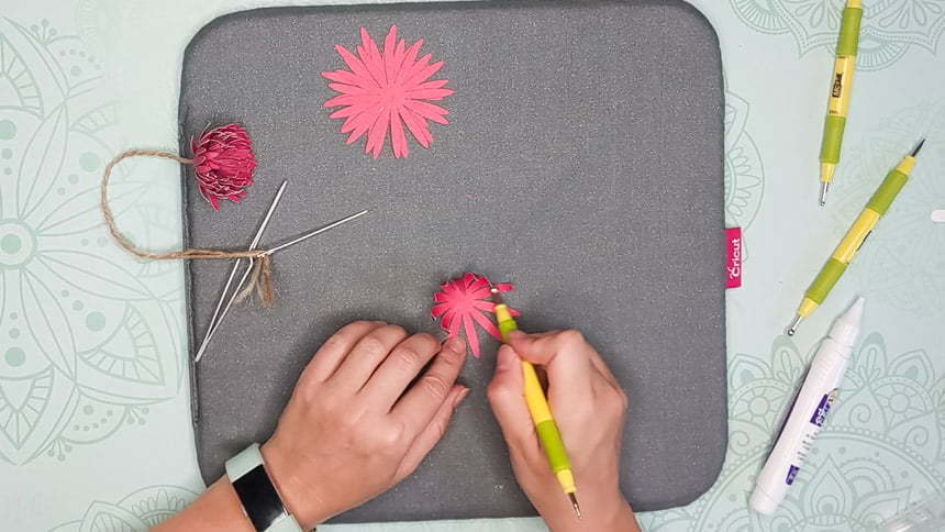 Applying pressure with the blossom tool from the extremity of the petal to make the DIY paper Chrysanthemum