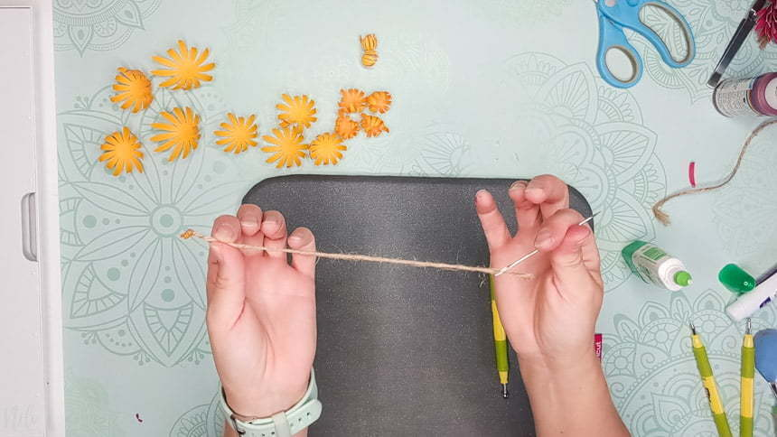 Threading the jute twine to make the DIY paper Chrysanthemum