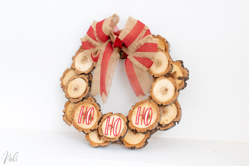 DIY wood slice wreath written Ho Ho Ho with vinyl.